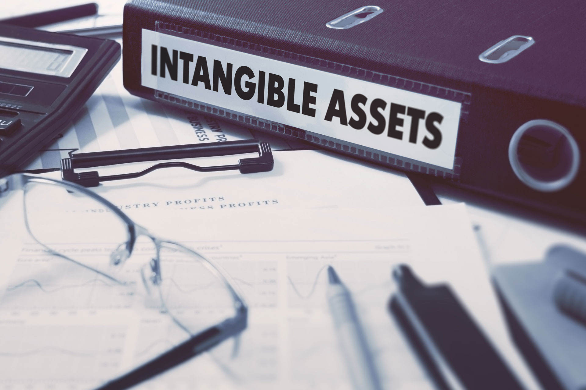 Office folder with inscription Intangible Assets on Office Desktop with Office Supplies. Business Concept on Blurred Background. Toned Image. - Image